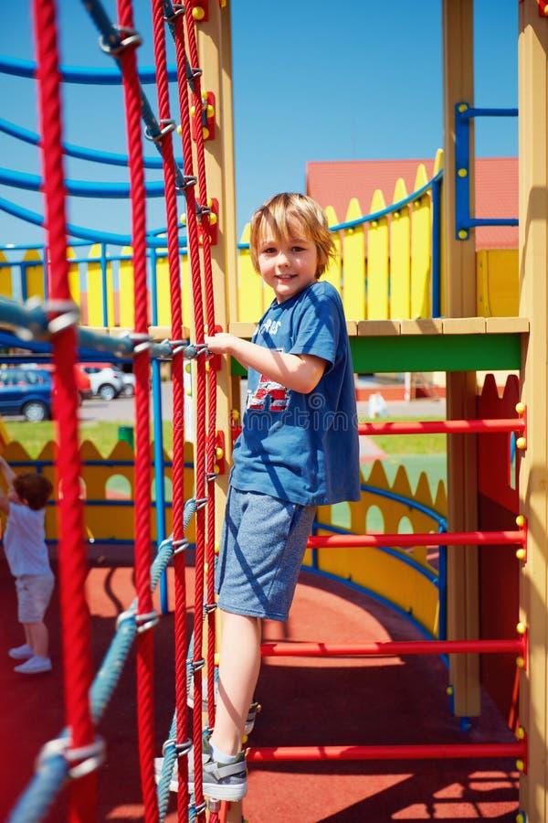 Niño feliz que sube la pared de la cuerda, jugando a juegos en patio colorido del castillo imagen de archivo