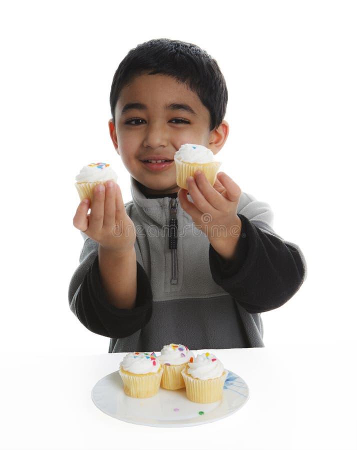 Niño feliz que tiene un banquete de magdalenas imagen de archivo libre de regalías