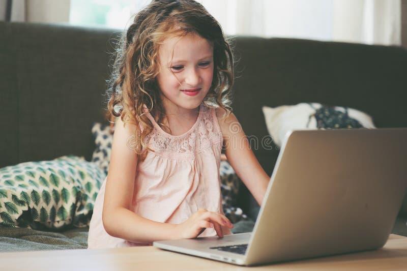 Niño feliz que usa el ordenador portátil en casa Colegiala que aprende con el ordenador y Internet imagenes de archivo