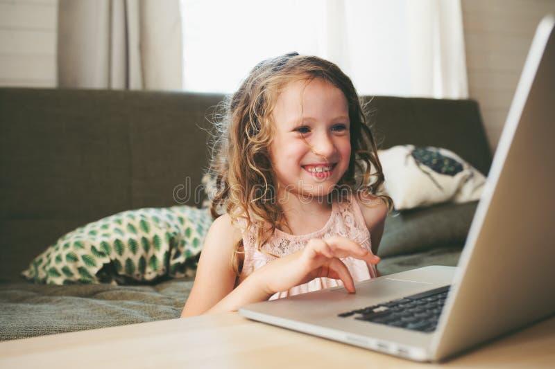 Niño feliz que usa el ordenador portátil en casa Colegiala que aprende con el ordenador y Internet fotos de archivo libres de regalías