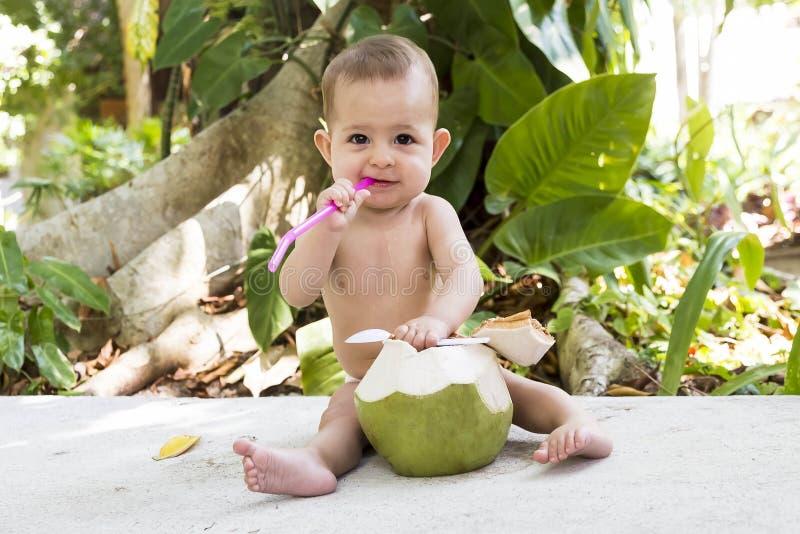 Niño feliz y bebé alegre en viaje Come y bebe el coco joven verde imagenes de archivo