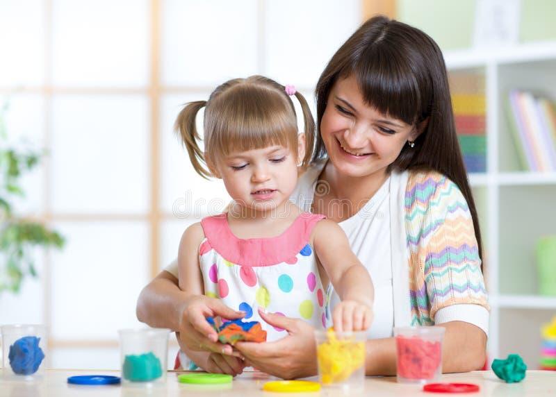 Niño feliz y madre que se sientan en la tabla y fotografía de archivo