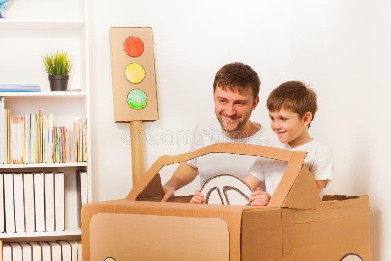 Niño feliz y su papá que conducen el coche de la cartulina del juguete fotografía de archivo libre de regalías