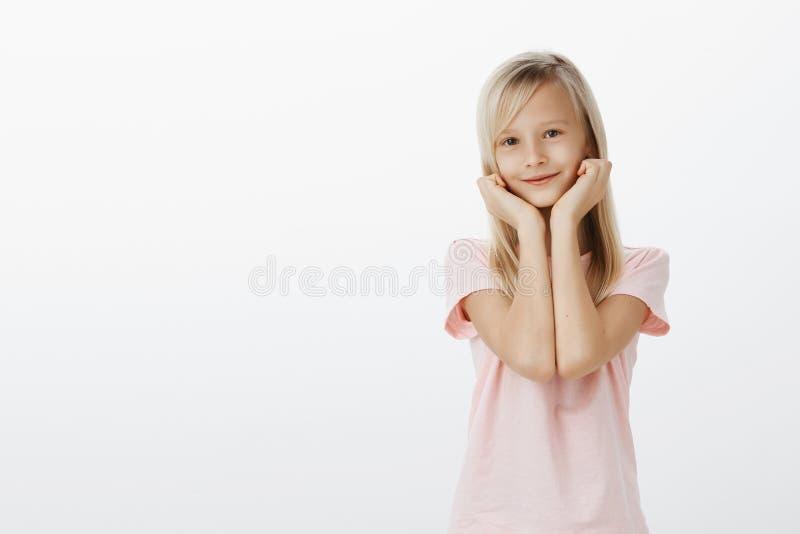 Niño femenino adorable lindo con el pelo rubio hermoso, la cabeza en las palmas y la sonrisa ampliamente, obediente que se inclin fotografía de archivo libre de regalías