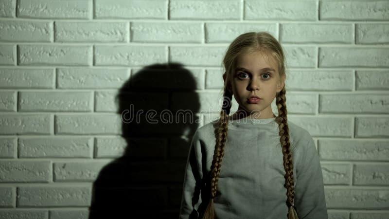 Ni?o femenino asustado que mira la c?mara, el concepto infantil de la fobia, del miedo y del horror imagen de archivo