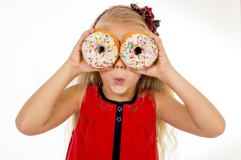 Niño femenino con el pelo rubio largo y el vestido rojo que juegan con el buñuelo de dos azúcares con los desmoches que los ponen imagen de archivo libre de regalías