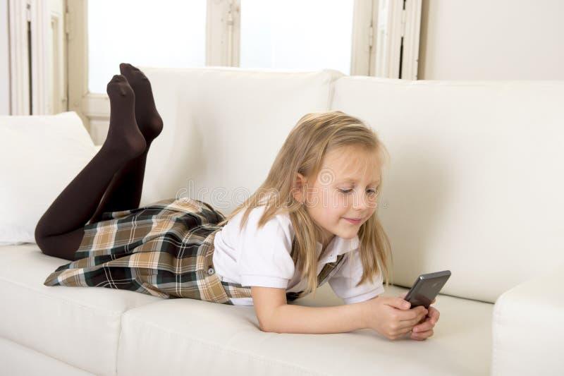 Niño femenino con el pelo rubio que miente en el sofá casero usando Internet app en el teléfono móvil fotografía de archivo