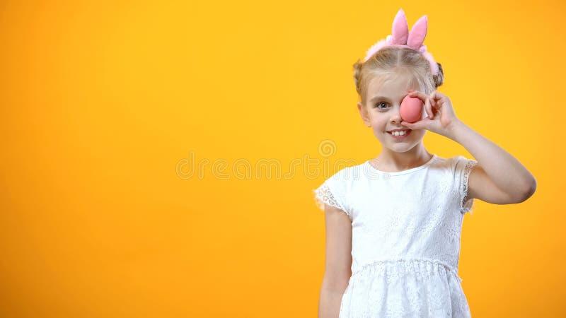 Niño femenino juguetón que sostiene el huevo coloreado delante del ojo, símbolo de Pascua, día de fiesta foto de archivo