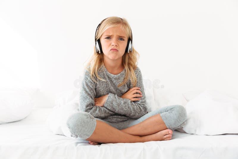 Niño femenino trastornado en los auriculares que se sientan con los brazos y la pierna cruzados fotos de archivo libres de regalías
