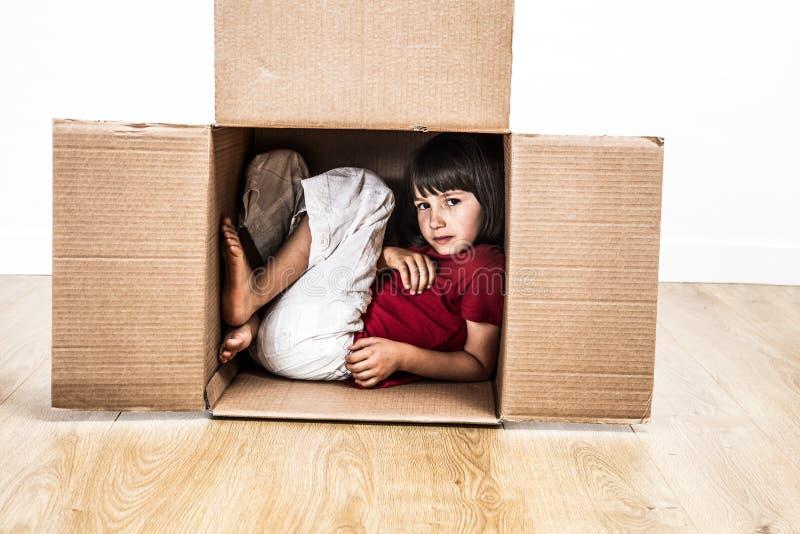 Niño fresco hunched en la caja de cartón que oculta en pequeña casa imagen de archivo