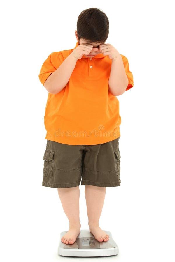 Niño gordo mórbidamente obeso en escala foto de archivo