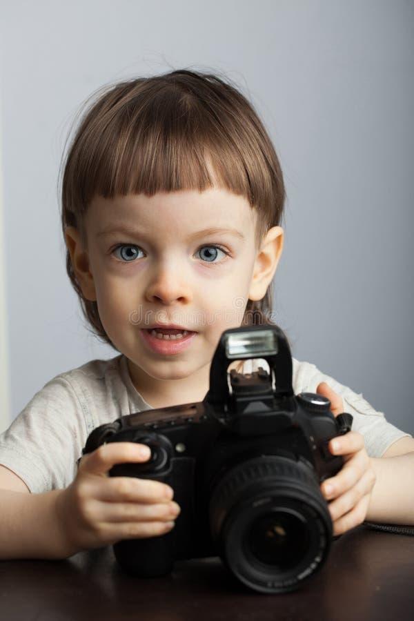 Niño hermoso adentro con la cámara profesional Niño pequeño con el pelo rubio largo que fotografía en el estudio fotos de archivo libres de regalías