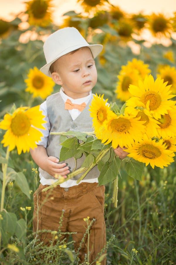 Niño hermoso con el girasol en campo de la primavera fotografía de archivo libre de regalías