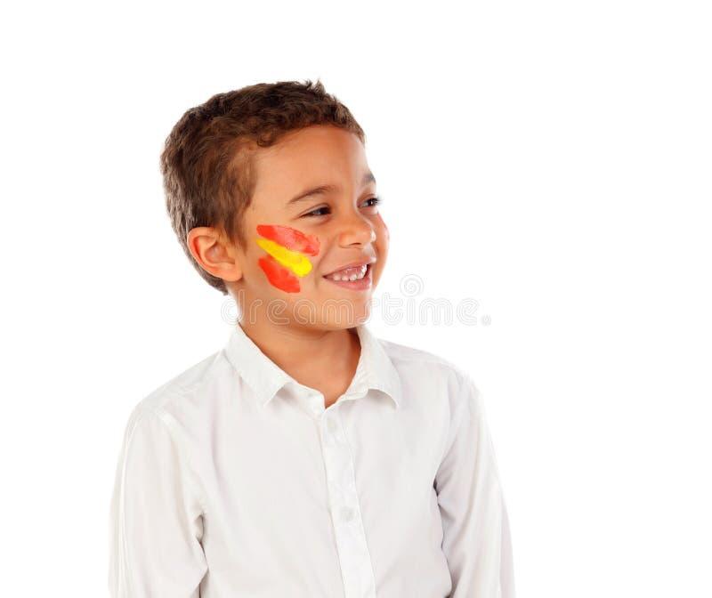 Niño hermoso con la bandera española de los colores pintada en su cara foto de archivo