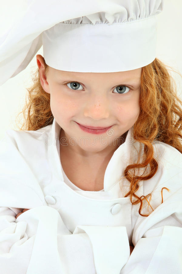 Niño hermoso de la chica joven en uniforme y sombrero del cocinero fotos de archivo