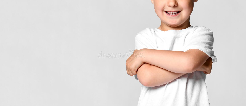 Niño hermoso del niño pequeño en una camiseta blanca, celebrando sus brazos cruzada y la sonrisa, colocándose en un fondo blanco fotografía de archivo