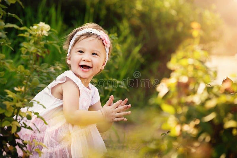 Niño hermoso en jardín que sonríe y que aplaude fotografía de archivo