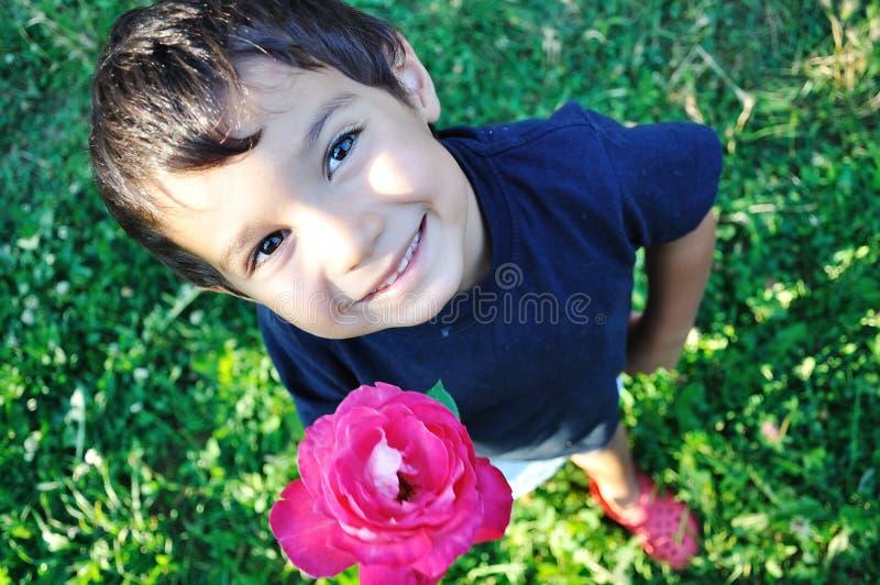 Niño hermoso feliz en la tierra con la rosa al aire libre imagen de archivo