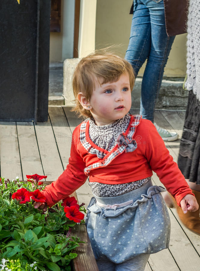 Niño hermoso joven de la muchacha, niño que juega en la calle de la ciudad antigua cerca de los macizos de flores con las flores  foto de archivo libre de regalías