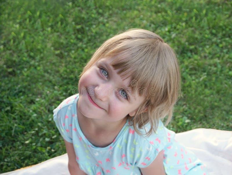 Niño hermoso lindo de la muchacha con los ojos verdes adorables que se sientan feliz en un prado verde fotos de archivo libres de regalías