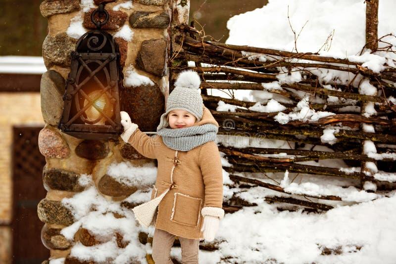 Niño hermoso muy dulce de la niña en una capa beige a sonriente imágenes de archivo libres de regalías