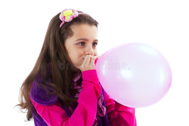 Niño hermoso que sopla un globo foto de archivo