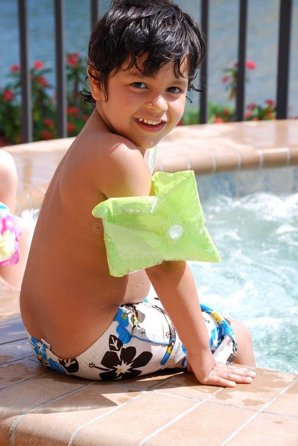 Niño hispánico adorable por la piscina foto de archivo