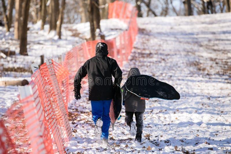 Niño hispánico que corre en la nieve lista al trineo imagen de archivo
