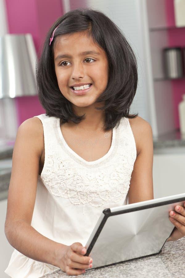 Niño indio asiático de la muchacha que usa el ordenador de la tablilla fotografía de archivo