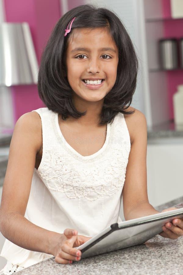 Niño indio asiático de la muchacha que usa el ordenador de la tablilla imagenes de archivo