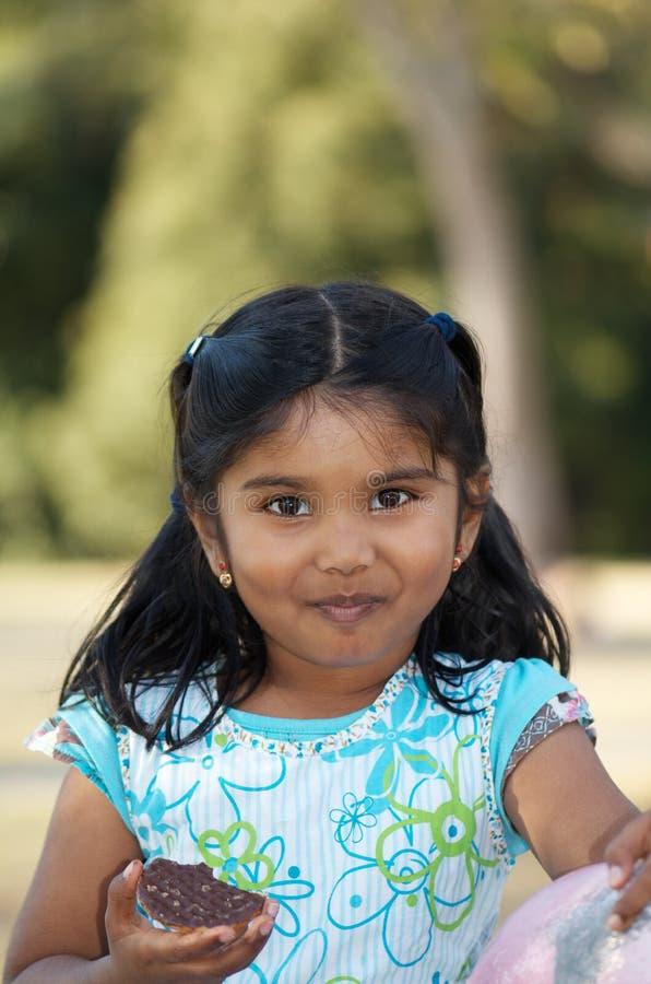 Niño indio lindo que come la galleta imagenes de archivo