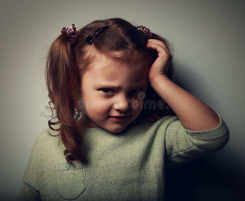 Niño infeliz con el dolor de cabeza que lleva a cabo la cabeza la cabeza vendimia fotografía de archivo