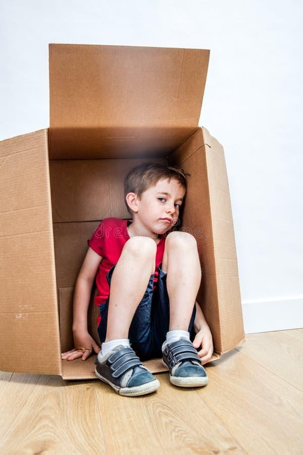 Niño infeliz que se sienta en la caja, buscando para el refugio del maltratamiento foto de archivo libre de regalías