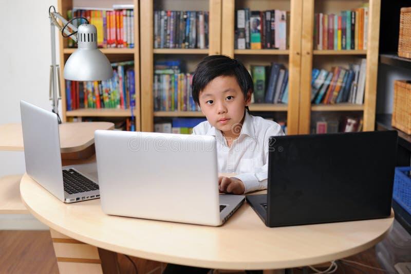 Niño inteligente que trabaja en los ordenadores múltiples fotos de archivo
