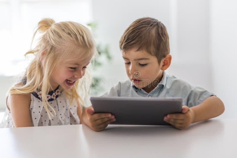 Niño joven adorable del hermano y de la hermana usando la tableta imagenes de archivo