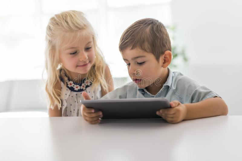 Niño joven adorable del hermano y de la hermana usando la tableta imágenes de archivo libres de regalías