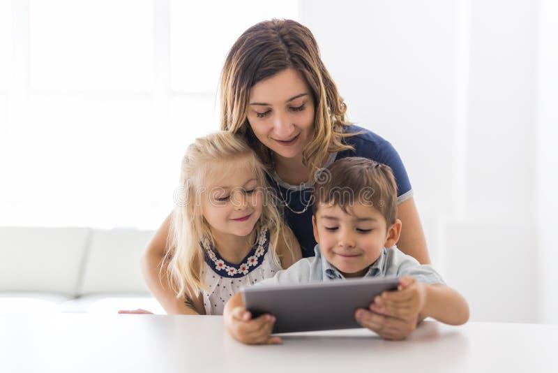 Niño joven adorable del hermano y de la hermana usando la tableta con la madre imagenes de archivo