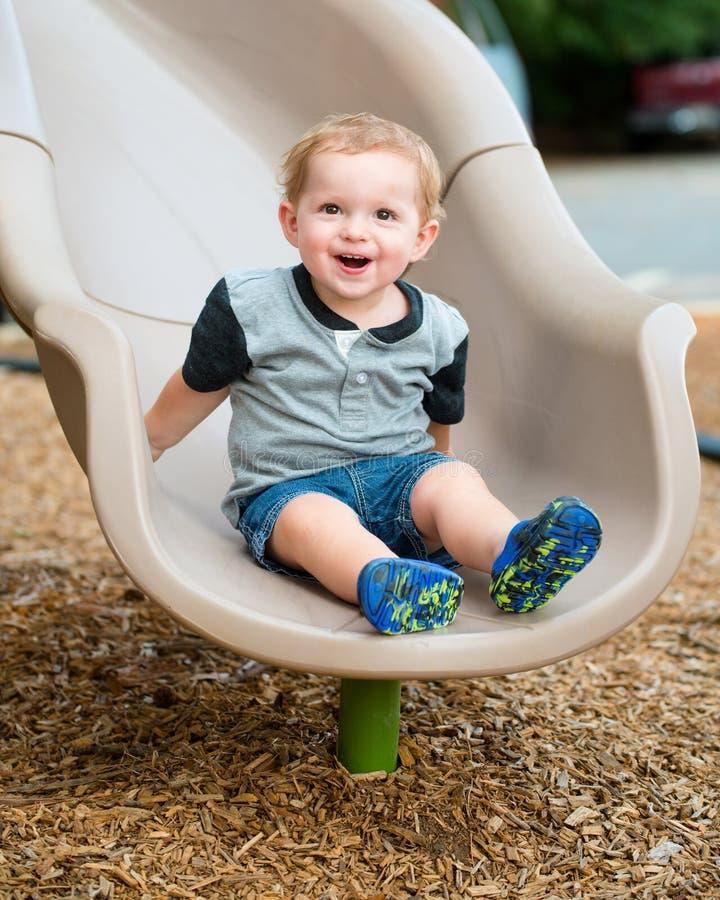 Niño joven del niño pequeño que juega en diapositiva fotos de archivo