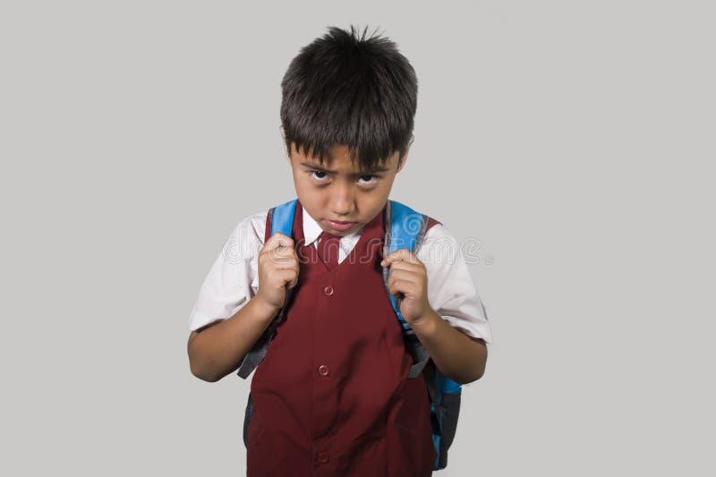 Niño joven en el uniforme escolar que siente mirada triste y deprimida abajo de la víctima asustada y avergonzada de tiranizar y  foto de archivo