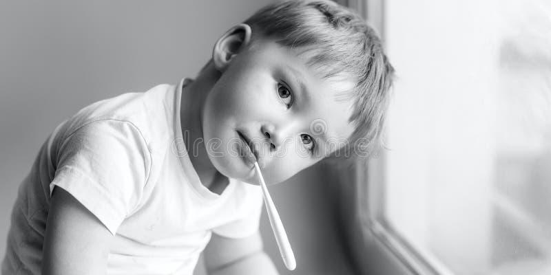 Niño joven enfermo con un thermomether, midiendo la altura de su fiebre y mirando en la foto blanco y negro de la cámara imagen de archivo