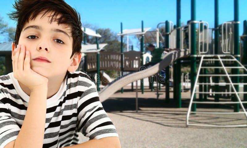 Niño joven hermoso del muchacho aburrido en el parque. fotografía de archivo