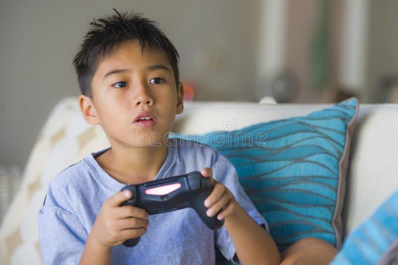 Niño joven latino 8 años emocionados y control remoto que se sostiene en línea feliz del videojuego que juega que goza divirtiénd fotos de archivo libres de regalías
