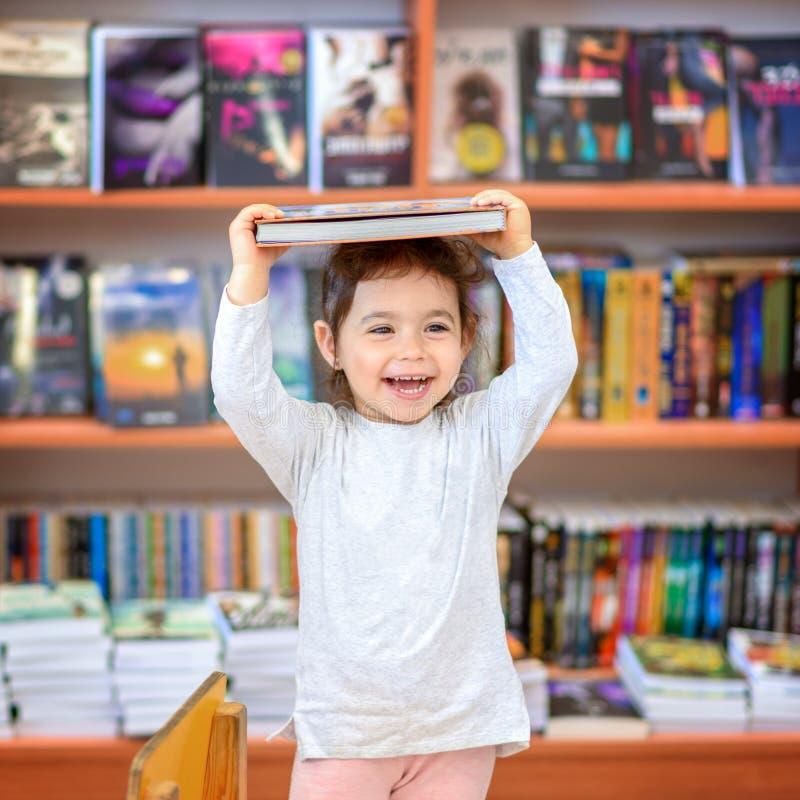 Niño joven lindo que coloca y que sostiene el libro en cabeza Niño en una biblioteca, tienda, librería foto de archivo