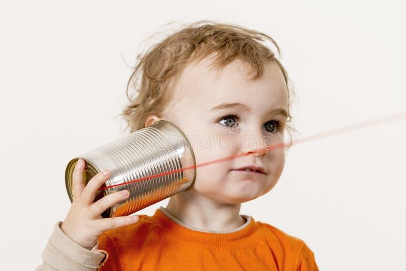 Niño joven que escucha el teléfono de la lata fotografía de archivo