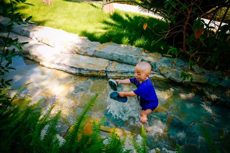Niño joven que juega afuera en el río imagenes de archivo
