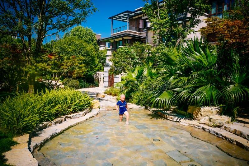 Niño joven que juega afuera en el río foto de archivo