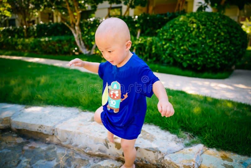 Niño joven que juega afuera en la corriente fotografía de archivo libre de regalías