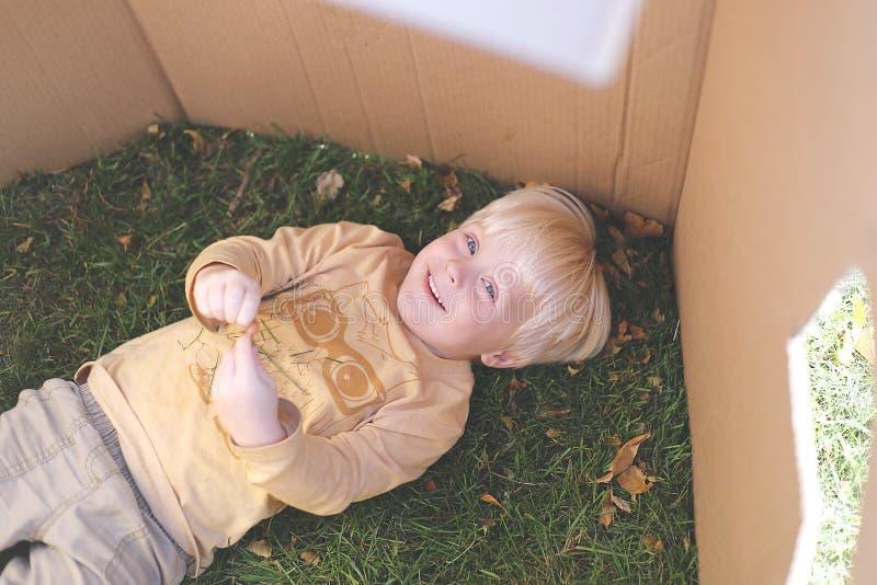 Niño joven que pone en hierba mientras que juega en fuerte de la caja de cartón imágenes de archivo libres de regalías