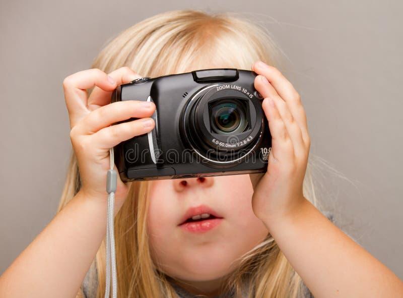 Niño joven que sostiene una cámara que toma un cuadro imágenes de archivo libres de regalías