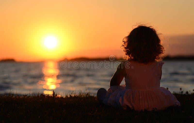 Niño joven relajante en puesta del sol fotos de archivo